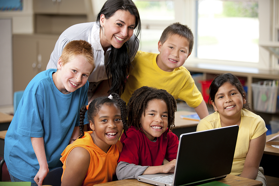 Teacher with students at a laptop computer