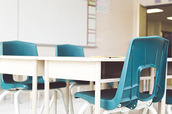 Three empty chairs in a classroom