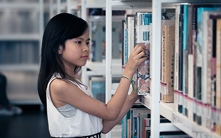 Child selecting book in library