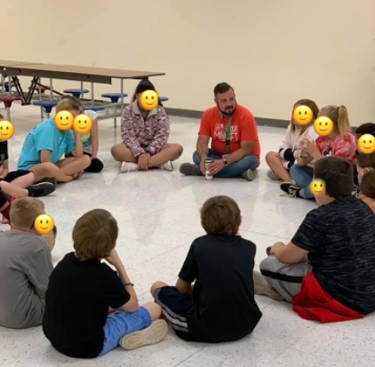 Seth Francis teaches students seated in a circle on the floor