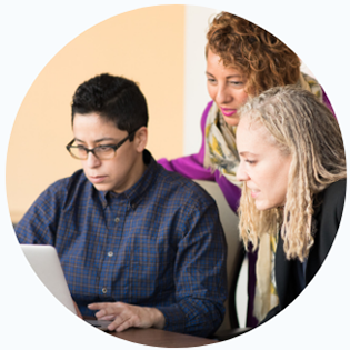 Man and two women around computer